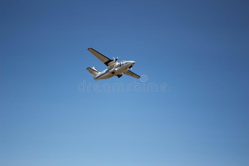 Het vliegtuig die in de blauwe hemel hangen royalty-vrije stock afbeeldingen
