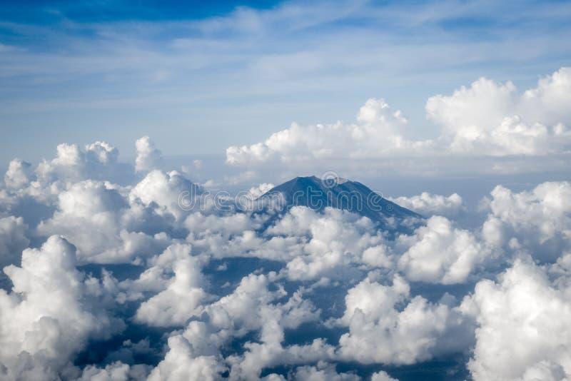 Het vliegtuig die hierboven zet Agung-vulkaan, Bali, Indonesië vliegen op stock fotografie