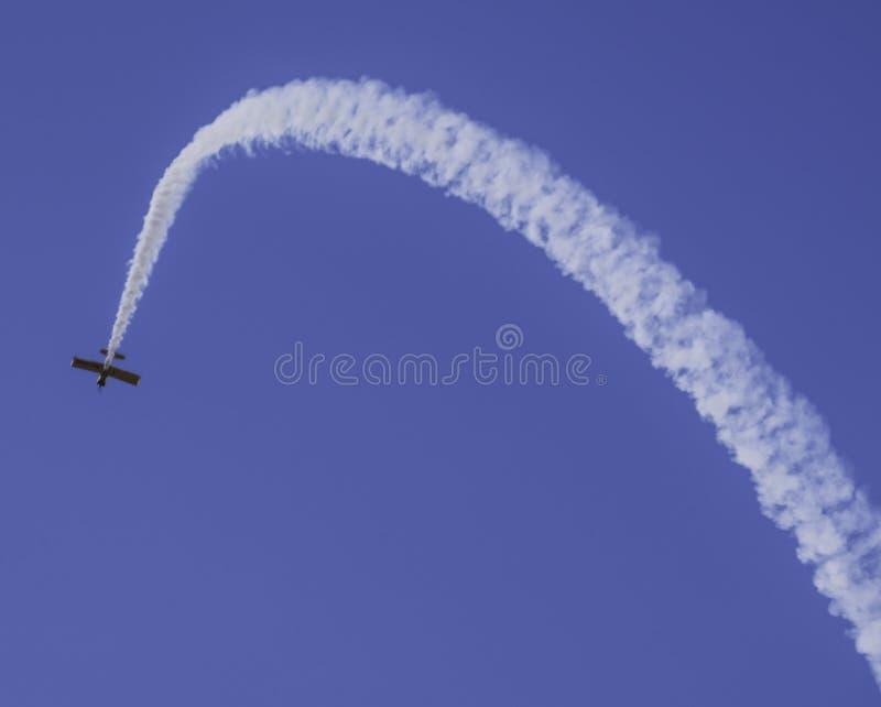 Het vliegtuig die rooksleep in lucht verlaten toont stock foto's