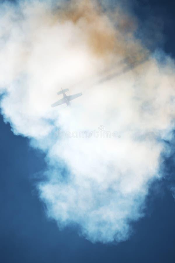 Het Vliegtuig in een rookwolk stock fotografie