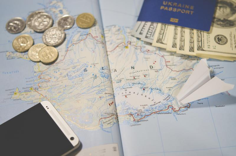 Het vliegtuig, smartphone, het biometrische paspoort, de dollars, de muntstukken en de creditcards liggen op een kaart stock fotografie