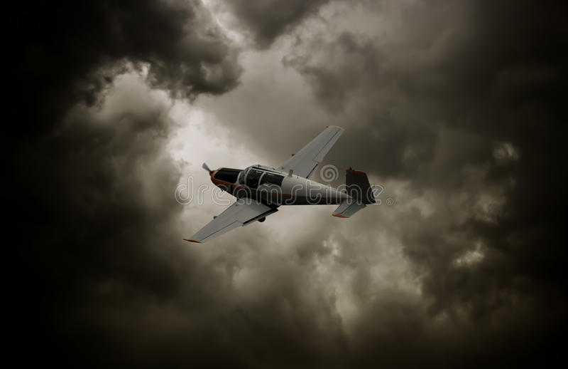 Het vliegtuig van de propeller met donkere wolken stock foto