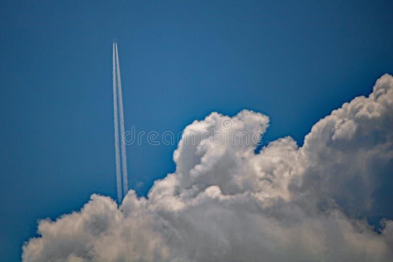 Het vliegtuig verlaat een Sleep knallend uit van achter Zware Wolk stock fotografie