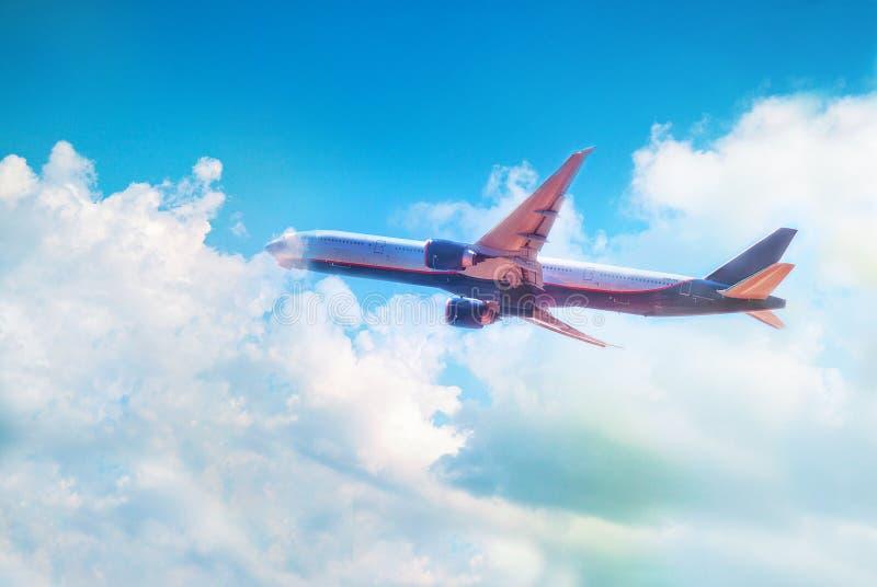 Het vliegtuig vliegt in een blauwe hemel met witte wolken royalty-vrije stock foto