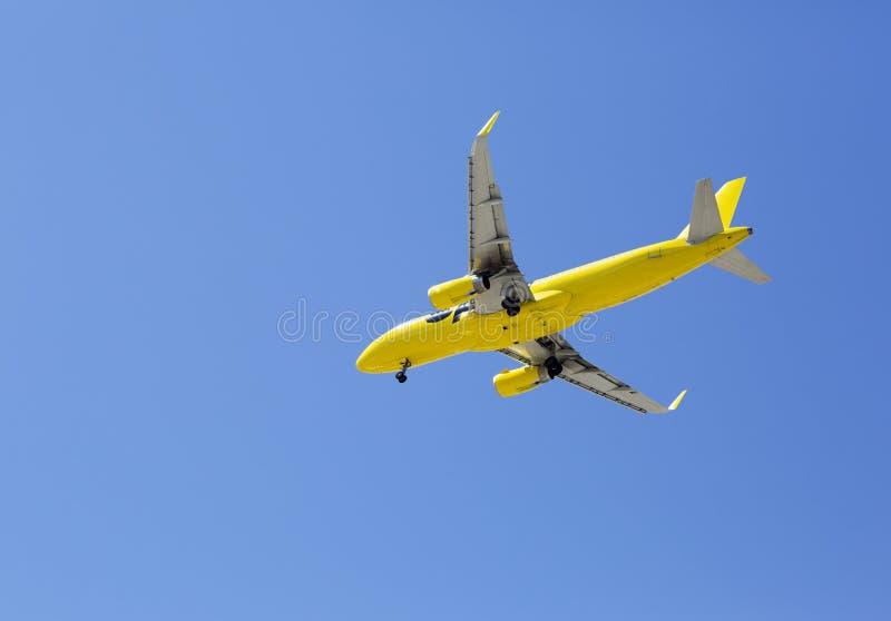 Het vliegtuig vliegt tegen de blauwe hemel royalty-vrije stock afbeelding
