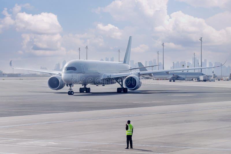 Het vliegtuig wordt geleid door grondpersoneel aan de parkerenplaats royalty-vrije stock foto's