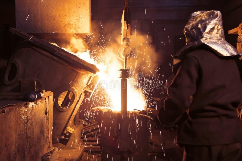 Het vloeibare metaal wordt gegoten in vormen Arbeiders controlerend smelten van metaal in ovens De arbeiders werkt bij royalty-vrije stock afbeelding