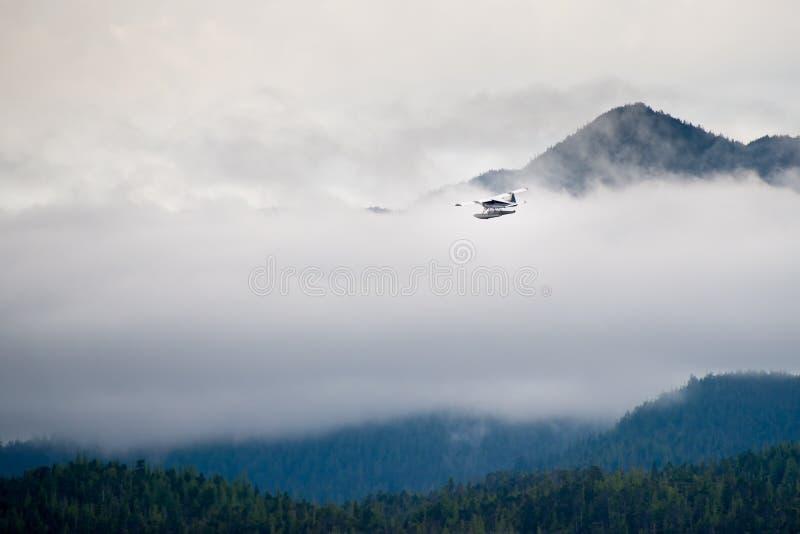 Het Vlottervliegtuig die van Alaska door Wolken vliegen stock foto
