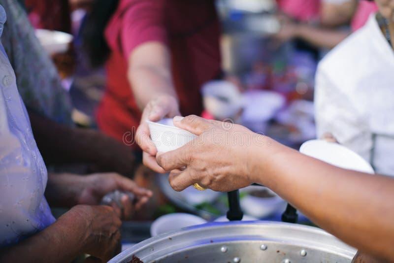 Het voeden Concepten: De hand bood aan om voedsel van een rijke manaandeel te schenken: Het concept het sociale delen: Armen die  royalty-vrije stock afbeelding