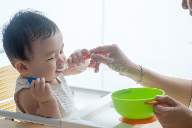 Het voedende kind van de moeder stock foto's