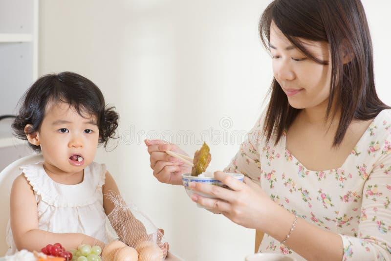 Het voedende kind van de moeder stock foto