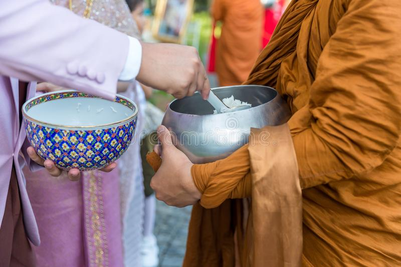 Het voedsel van de aanbieding aan monnik De bruidegom geeft aalmoesvoedsel aan een Boeddhistische monnik in traditionele Thaise h stock foto