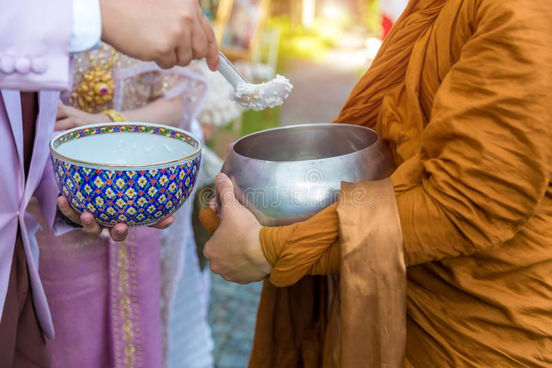 Het voedsel van de aanbieding aan monnik De bruidegom geeft aalmoesvoedsel aan een Boeddhistische monnik in traditionele Thaise h royalty-vrije stock foto