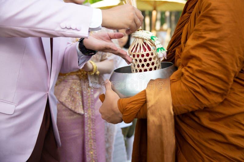 Het voedsel van de aanbieding aan monnik De bruidegom geeft aalmoesvoedsel aan een Boeddhistische monnik in traditionele Thaise h stock fotografie