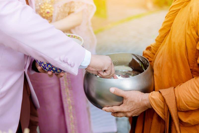 Het voedsel van de aanbieding aan monnik De bruidegom geeft aalmoesvoedsel aan een Boeddhistische monnik in traditionele Thaise h royalty-vrije stock foto's