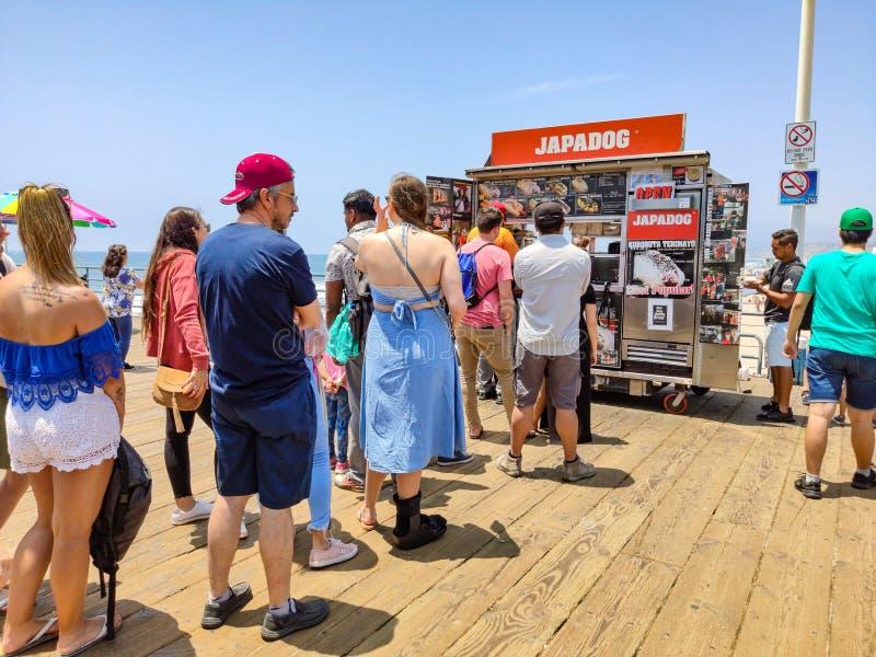 Het voedsel van de Japadogstraat, Mensenrij wacht op de houten pijler van Santa Monica, traditionele winkel voor hotdogs stock afbeelding