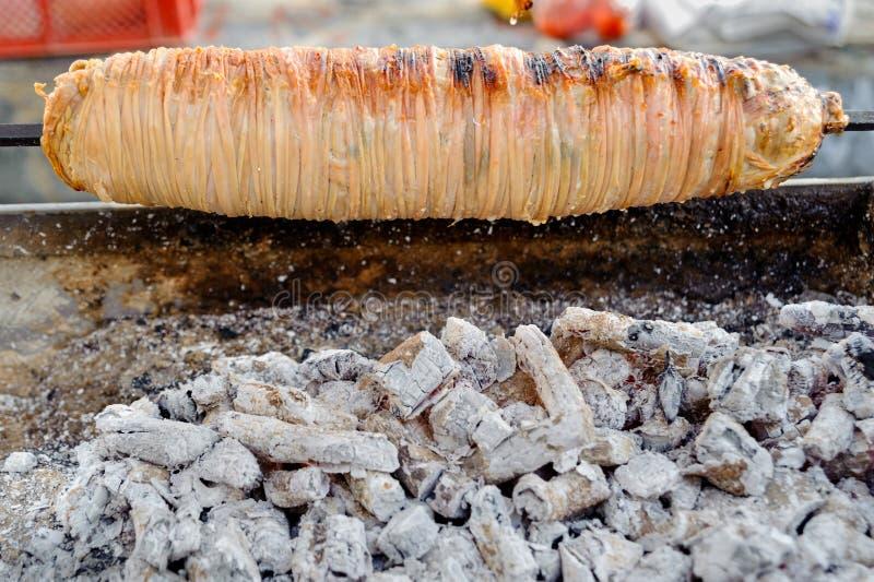 Het voedsel van de lamsdarm op vleespen, Turkse Kokorec bij peddlar barbecue in Istanboel Turkije wordt vastgebonden dat stock foto