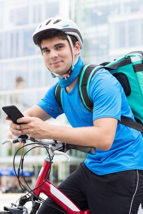 Het Voedsel van koerierson bicycle delivering in Stad die Mobiele Telefoon met behulp van royalty-vrije stock afbeeldingen
