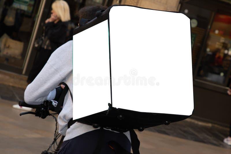 Het Voedsel van koerierson bicycle delivering in Stadsstraat met lege witte lege zak stock foto