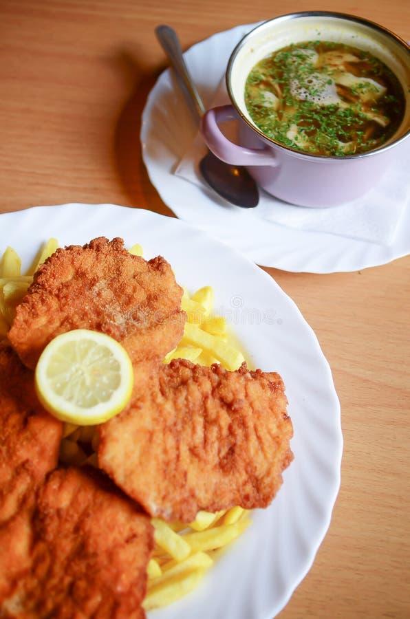 Het voedsel van Wenen - Worstjeschnitzel met frieten en plak van citroen, gebraden varkenskotelet, de Schnitzel van Figlmà ¼ ller stock afbeeldingen