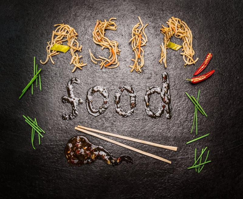 Het voedselinschrijving van Azië van noedels en saus met eetstokje en rode Spaanse peper op donkere leiachtergrond royalty-vrije stock afbeelding