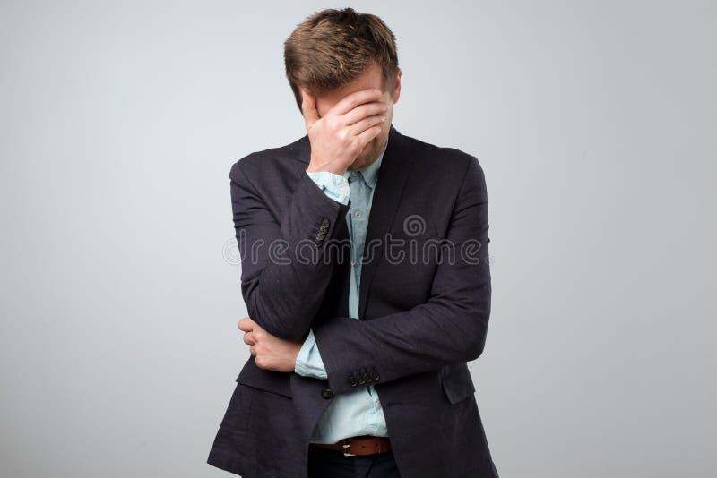 Het voelen van gedeprimeerd concept Uitgeputte jonge mens in kostuum die gezicht behandelen met hand stock fotografie
