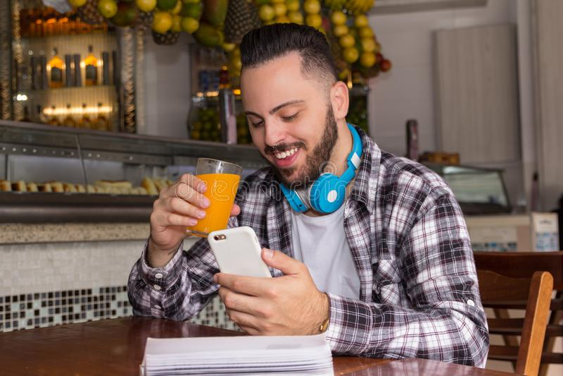 Het voer van de de lezingspret van de reizigersmens op sociaal netwerk en holdingsglas sap in openlucht in lijst van Braziliaans  royalty-vrije stock foto's