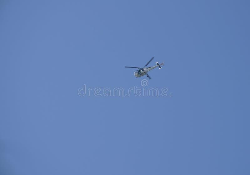 Het voertuig de helikopter tijdens de vlucht tegen de achtergrond van blauw de hemel stock foto's