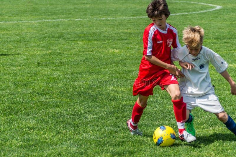 Het voetbal van jonge geitjes stock foto