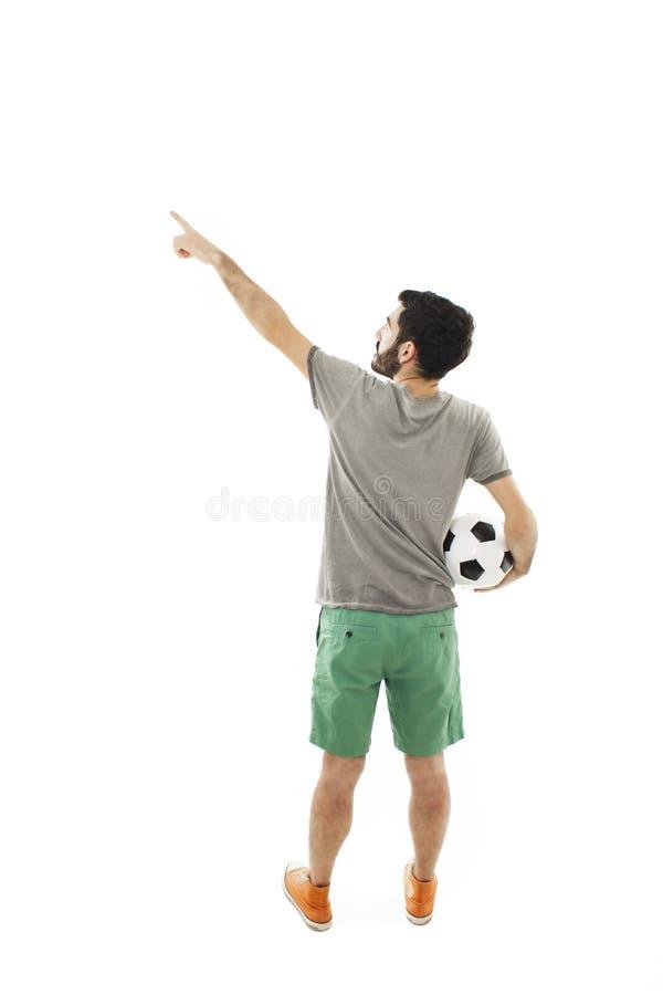 Het voetbalbal van de jonge mensenholding, het richten Achter mening stock foto's