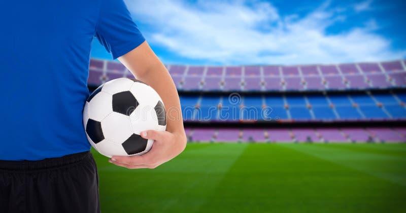 Het voetbalbal van de voetbalsterholding op gebied van groot stadion stock afbeelding