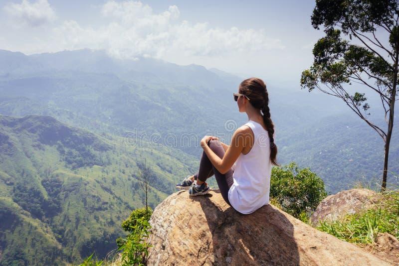 Het volgen toeristenavontuur Vrouwenzitting op de bovenkant van Ella-rots, Sri Lanka stock afbeeldingen