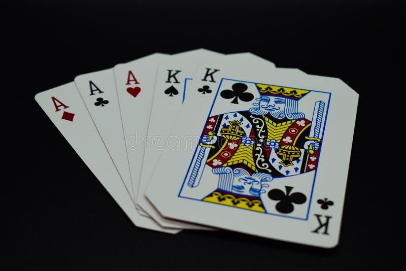 Het volledige hoogtepunt van huisazen van koningen van kaarten in pookspel tegen zwarte achtergrond stock fotografie