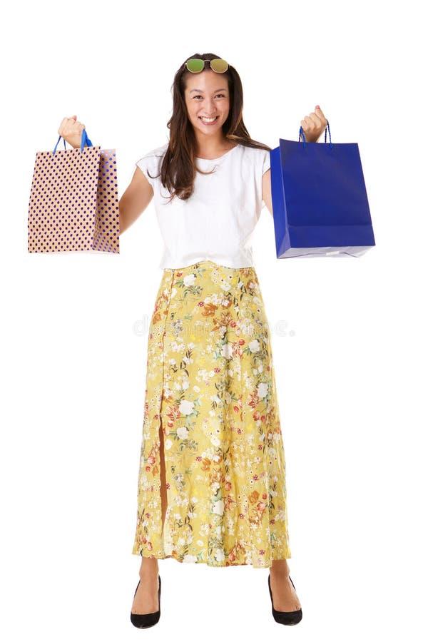 Het volledige lengte modieuze jonge Aziatische vrouw stellen met het winkelen zakken tegen geïsoleerde witte achtergrond royalty-vrije stock fotografie
