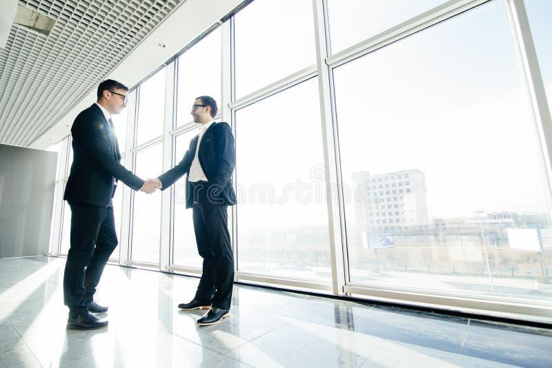 Het volledige lengte zijaanzicht van zakenlieden het schudden dient bureauvensters in royalty-vrije stock afbeelding