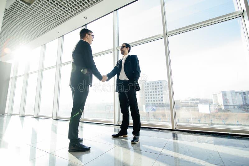 Het volledige lengte zijaanzicht van zakenlieden het schudden dient bureauvensters in stock foto