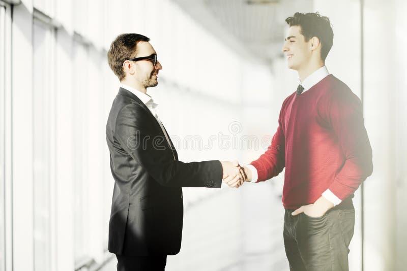 Het volledige lengte zijaanzicht van zakenlieden het schudden dient de bureaubouw in stock foto's