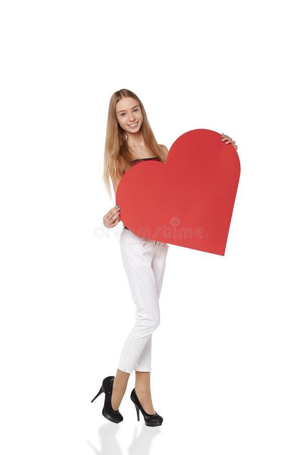 Het volledige lengtemeisje die een rood kartonhart steunen, ioslated op w royalty-vrije stock fotografie