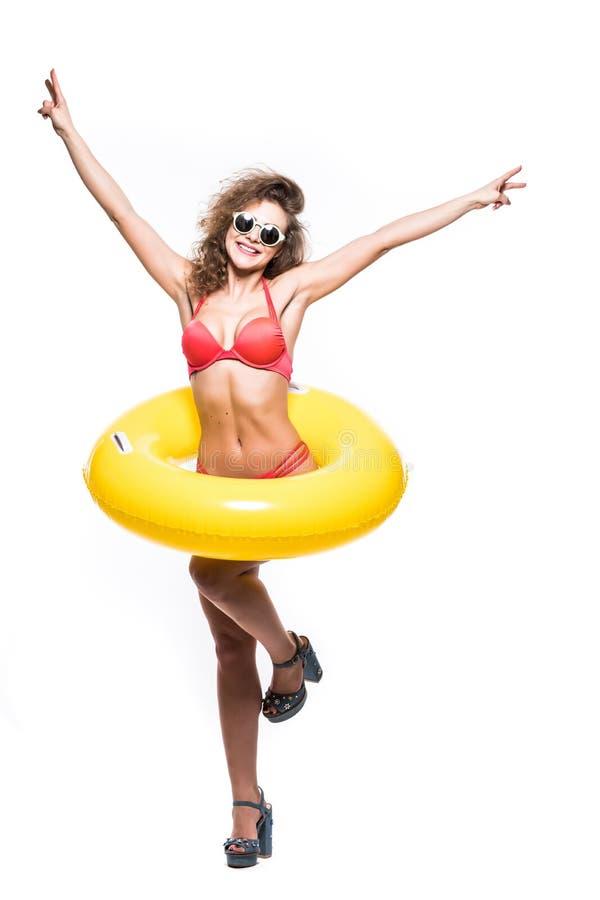 Het volledige lengteportret van een gelukkig meisje gekleed in zwempak in zonnebril reised handen met opblaasbare ring terwijl op royalty-vrije stock foto's