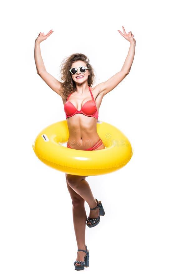 Het volledige lengteportret van een gelukkig meisje gekleed in zwempak in zonnebril reised handen met opblaasbare ring terwijl op stock foto's