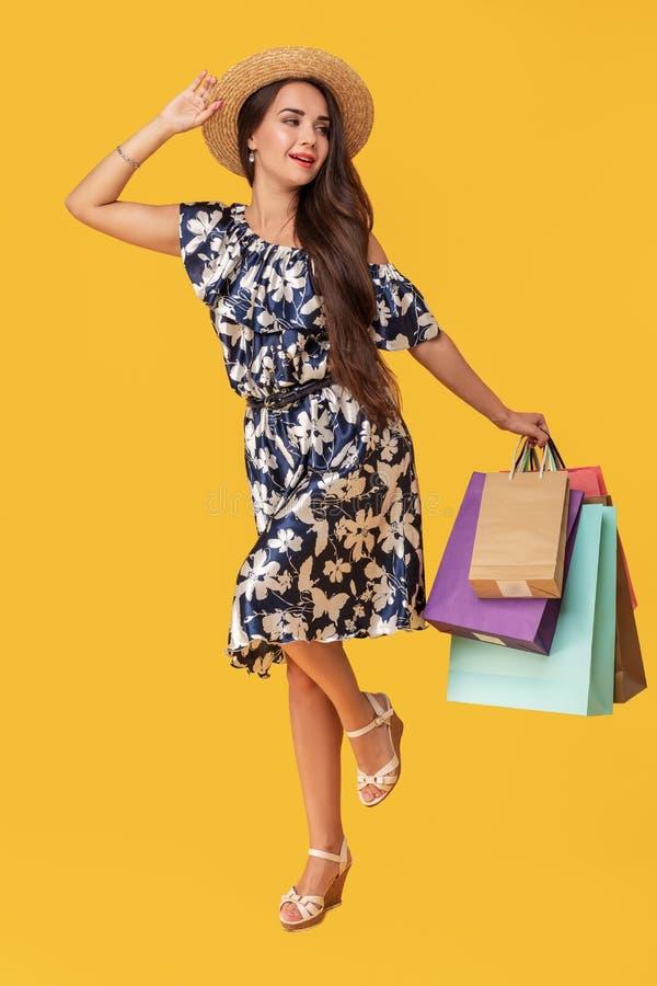 Het volledige lengteportret van een het glimlachen jong brunette in van de de zomerhoed en kleding holding het winkelen zakken is royalty-vrije stock foto