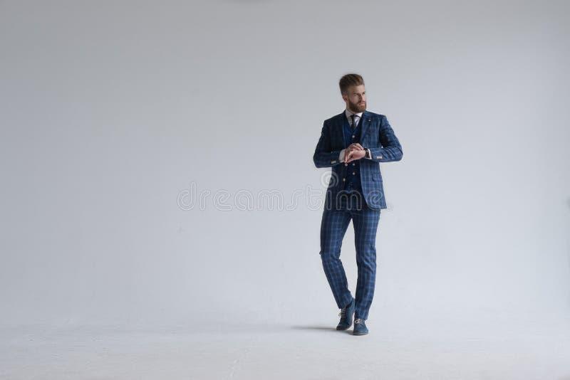 Het volledige lengteschot van jonge gebaarde modieuze zakenmanleider kleedde zich binnen in drie-stuk kostuum controlerend de tij royalty-vrije stock afbeelding