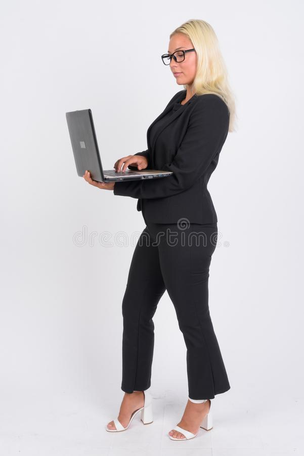 Het volledige lichaam schoot profielmening van jonge blondeonderneemster gebruikend laptop stock afbeeldingen