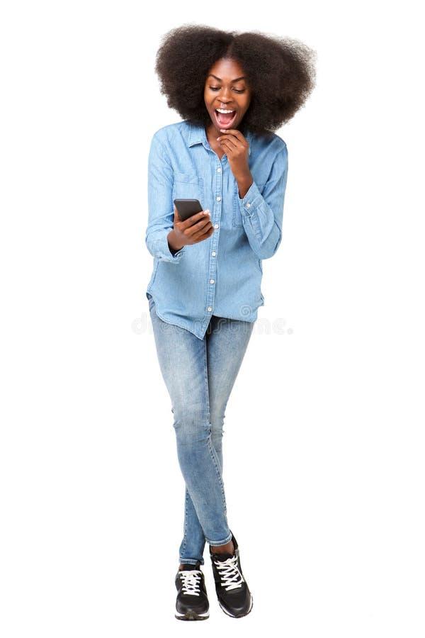 Het volledige lichaam verraste jonge vrouw die mobiele telefoon bekijken royalty-vrije stock afbeelding
