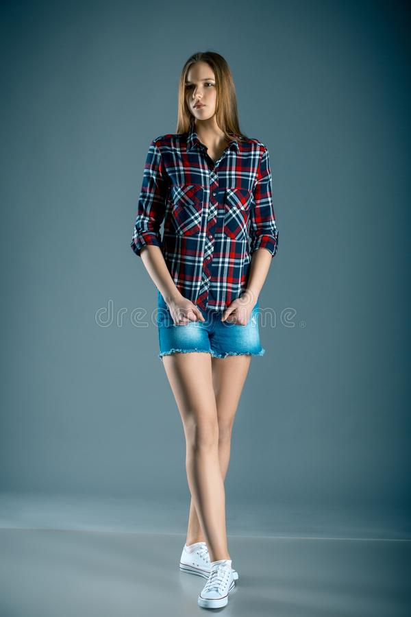 Het volledige meisje van de lengte mooie tiener in van het plaidoverhemd en denim borrels stock afbeelding