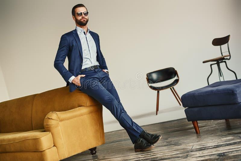 Het volledige portret van de lengtemanier van aantrekkelijke gebaarde zakenman in zonnebril die zich op kantoor bevindt en weg ki royalty-vrije stock foto