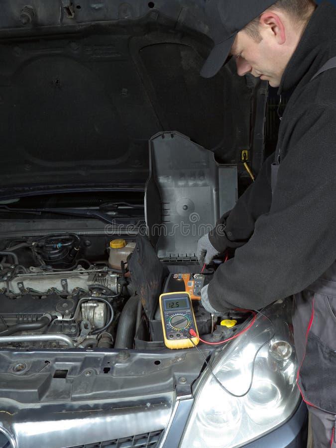 Het voltage van de autobatterij het controleren stock afbeeldingen