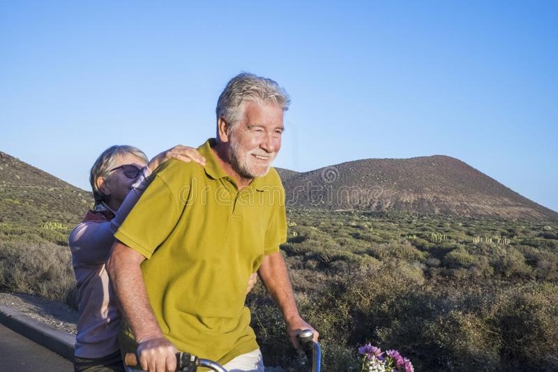 Het volwassen hogere Kaukasische paar gaat fiets glimlachend en hebbend heel wat pret samen, vakantie of alternatief teruggetrokk royalty-vrije stock afbeelding