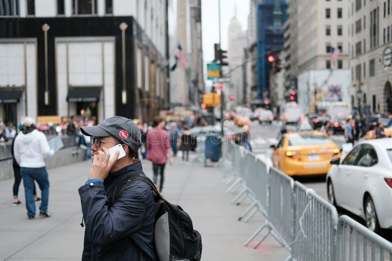 Het volwassen mannetje gezien gebruiken goed - bekende smartphone in New York royalty-vrije stock afbeelding
