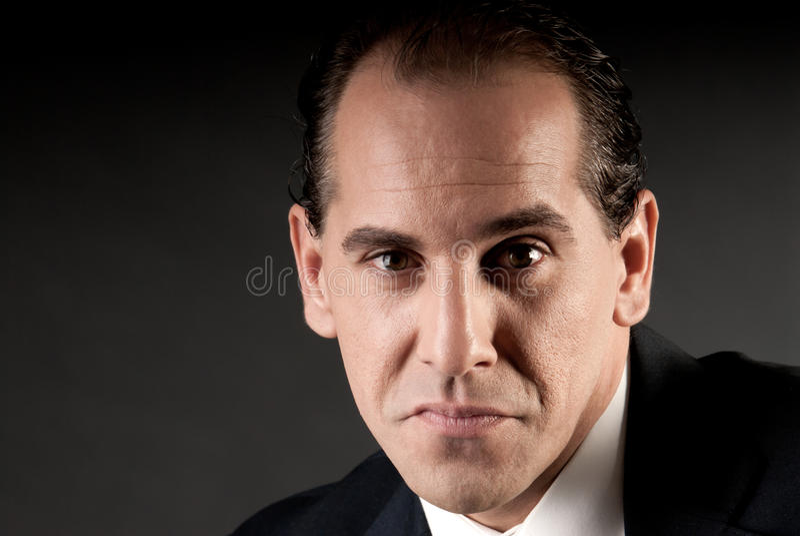 Het volwassen portret van de zakenmanclose-up op dark royalty-vrije stock afbeelding